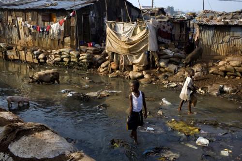 Boy walks through the river in kroo bay slum looking for scrap metal