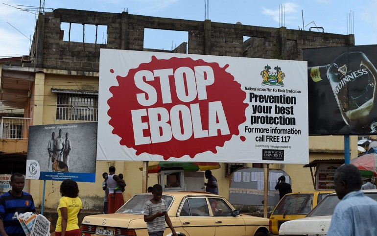 """(FILES) This file picture dated November 7, 2014 shows people walking past a billboard reading """"Stop Ebola"""" in Freetown. Sierra Leone said on March 19, 2015 it will confine around 2.5 million people to their homes across the capital and in the north in a three-day shutdown aimed at stemming the Ebola epidemic. AFP PHOTO/ FRANCISCO LEONGFRANCISCO LEONG/AFP/Getty Images"""
